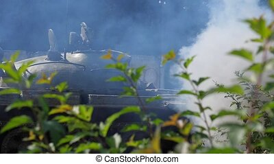 Smoke cloud from war tank on battle field. Military vehicle...