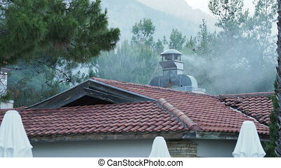 Smoke coming out of chimney on roof. Ventilation turbine is working . Extraction of steam and smoke from the kitchen.