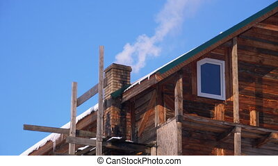 Smoke from a Brick Chimney on a Roof of Wooden House in Winter in the Mountains against a Blue Sky. Sunny Day. Traditional Smoking chimney. Wood fire-heated house. Old stone chimney smoking. Ukrainian village, Carpathians.