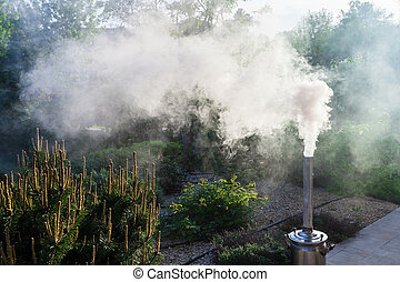 Smoke from a samovar pipe on backyard