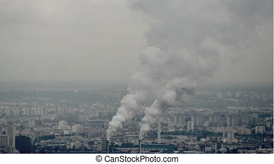 smoke from an industrial chimney, in the middle of the paris skyline, france
