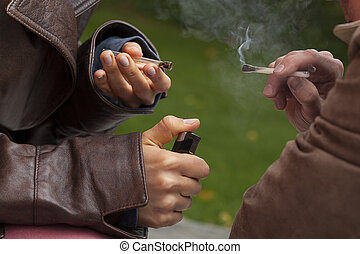 Close up of hands holding two burninig joints and thick smoke