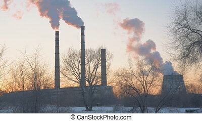 Smoke from factory chimneys on background of sunset sky