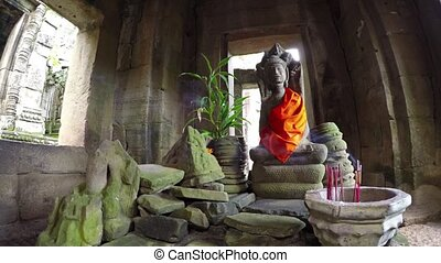 Smoke from incense drifts through an ancient hall before a sacred altar in Bayon Temple, an important historical site in Cambodia. UltraHD video