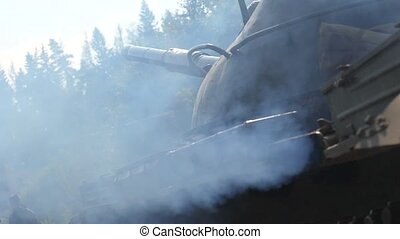 Smoke from military tank standing on war field. Military...