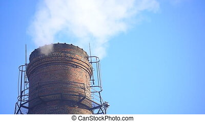 Smoke From the factory chimney against the blue sky