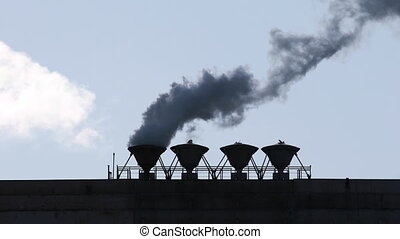 Smoke Goes From Pipe in the backlighting on the background of blue sky, industry and pollution concept