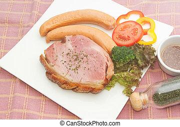 smoke ham steak with smoked sausage on the white plate