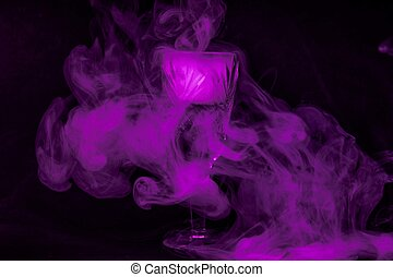 Smoke into cocktail glass on a black background. Witch potion background for Halloween. Unusual bar drink.