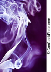 The graceful swirls of smoke from burning insence illuminated with purple color.