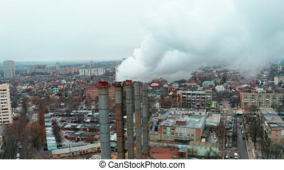 Smoke pollution from the pipes of the old boiler heating station in the center of the industrial district in city. White thick smoke from the pipes of the thermal station - Rising Shot