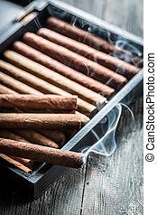 Smoke rising from a burning cigar on wooden humidor