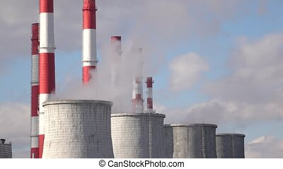 Smoke stacks and cooling towers against cloudy sky