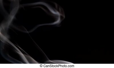 Smoke streaming in the dark from a burning incense stick. ...