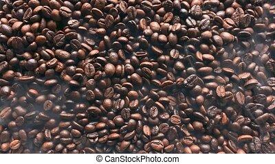 Smoke swirls over hot coffee beans. Top view.