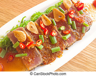 smoke tuna spicy with salad frieze on wooden table