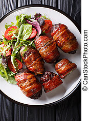 Smoked Armadillo eggs with jalapeno and cheese wrapped in bacon served with fresh salad close-up on a plate. Vertical top view
