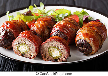 Smoked Armadillo eggs wrapped in bacon served with fresh salad close-up on the table. horizontal