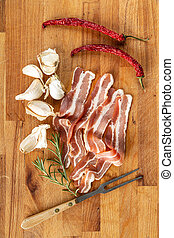 Smoked bacon strips, garlic, rosemary and chili peppers on cutting board.