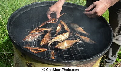 smoked fish delicacy - man hand take fresh delicacy smoked...