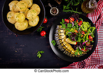 Smoked mackerel, boiled potatoes and fresh salad on dark background. Top view