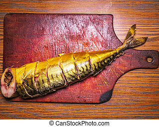 Smoked mackerel fish on a wooden cutting board.