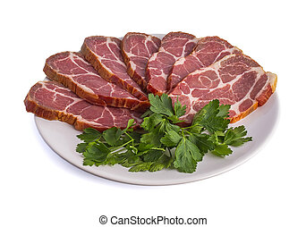 Smoked meat cut into pieces laid out on a dish with parsley