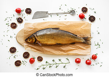 Smoked Omul fish decorated with herbs, baby tomatoes and dried lemon slices.