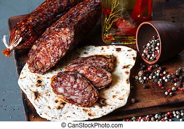 Smoked salami with pita and spices on a wooden cutting board on dark background