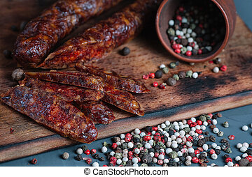 Smoked salami with spices on a wooden cutting board on dark background