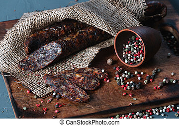 Smoked salami wrapped in a brown canvas and spices on a wooden cutting board on dark background