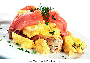 Scrambled eggs with smoked salmon, garnished with dill and parsley. A delicious breakfast treat!
