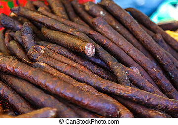 Smoked sausages for sale on a market.