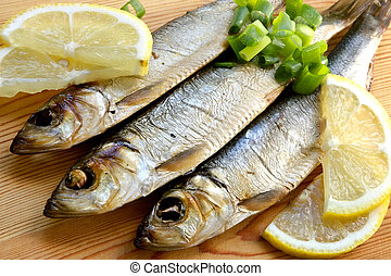 Smoked sprat-appetizing snack with a lemon and a green onions