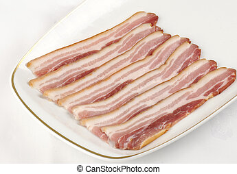 a white plate with strips of uncooked smoked streaky bacon