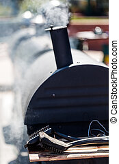 Smoker - Large barbecue smoker cooking meat.