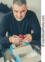 Smoker man roll tobacco cigarettes using rolling machine