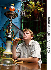 Smoker - Man smoking a traditional Middle Eastern Hookah.