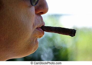 smoker with glasses and smokes the cigar 2