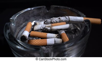 Smokes a cigarette in an ashtray in front of the camera