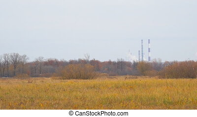 Smokestacks in distance on the background of autumn meadows