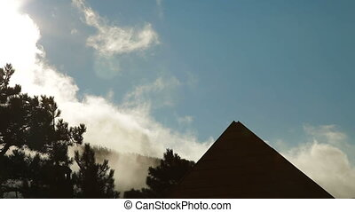 smokey hill - smoke covered forest and roof of house on the...