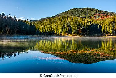smokey lake reflect forest mountain and blue sky. orange...