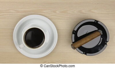 Smoking a cigar and drinking a cup of hot coffee.