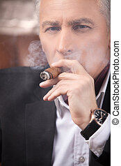 Smoking a cigar. Successful mature businessman smoking a cigar and looking at camera