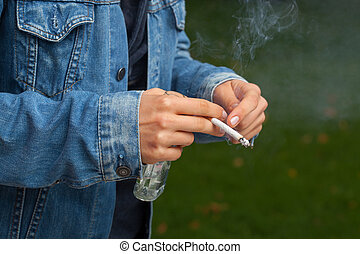 Smoking a cigarette and drinking - Teenager smoking a...