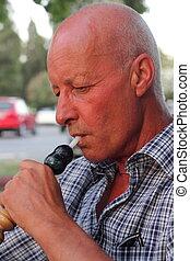 portrait of a man smoking a hookah waterpipe in a Turkish bazaar