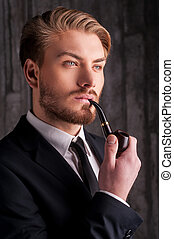 Smoking a pipe. Portrait of handsome young man in formalwear smoking a pipe and looking away