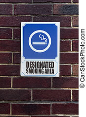 Smoking area sign on a brick wall