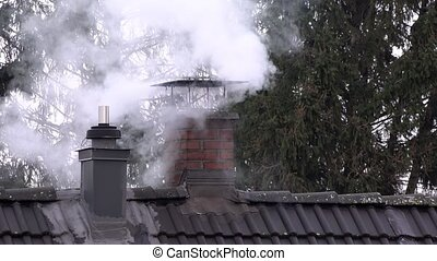 Smoking chimney and pipe on the top of a house with heat flicker